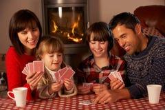 Retrato de las tarjetas que juegan de la familia por el fuego de registro acogedor Foto de archivo