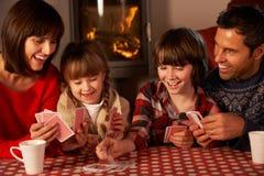 Retrato de las tarjetas que juegan de la familia por el fuego de registro acogedor Imagenes de archivo