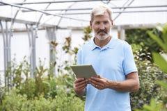 Retrato de las ventas auxiliares en centro de jardinería con la tableta de Digitaces Imágenes de archivo libres de regalías