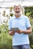 Retrato de las ventas auxiliares en centro de jardinería con la tableta de Digitaces Imagen de archivo libre de regalías
