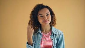 Retrato de ligar sonriente de la señora afroamericana carismática tocando el pelo metrajes