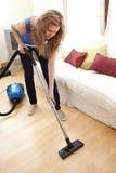 Retrato de limpiar con la aspiradora de la mujer joven fotos de archivo