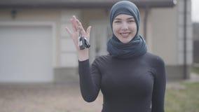 Retrato de llevar que celebra y que agita musulmán joven sonriente confiado acertado independiente de la mujer del coche de las l almacen de metraje de vídeo