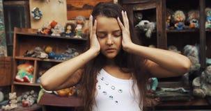 Retrato de los 10 años de la muchacha El niño extraño está tocando su cabeza y está mirando profundamente la cámara Jardín por co metrajes