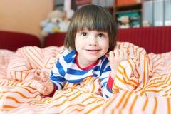 Retrato de los 2 años lindos de niño en cama en casa Fotografía de archivo