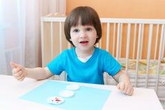Retrato de los 2 años preciosos de muchacho que hace el muñeco de nieve del cojín de algodón Foto de archivo libre de regalías
