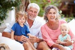 Retrato de los abuelos que se sientan al aire libre con los nietos fotografía de archivo