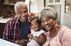 Retrato de los abuelos que se sientan con la nieta del bebé alrededor de la tabla en casa imágenes de archivo libres de regalías