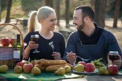 Retrato de los adultos jovenes que beben el vino al aire libre Imágenes de archivo libres de regalías