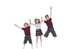 Retrato de los alumnos felices que llevan a cabo las manos mientras que salta sobre el fondo blanco Foto de archivo libre de regalías