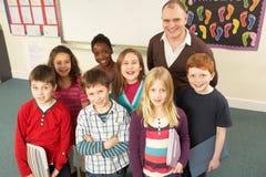 Retrato de los alumnos que se colocan en sala de clase Foto de archivo libre de regalías