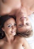 Retrato de los amantes hermosos sonrientes que presentan en cama Foto de archivo libre de regalías