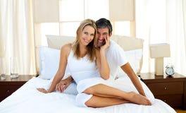 Retrato de los amantes que se sientan en cama Fotos de archivo