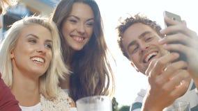 Retrato de los amigos alegres que hacen la foto del selfie en smartphone en patio trasero del jardín almacen de metraje de vídeo