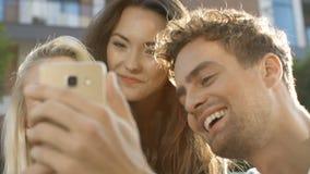 Retrato de los amigos alegres que hacen la foto del selfie en smartphone en patio trasero del jardín almacen de video