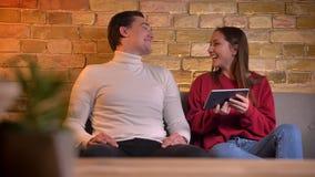 Retrato de los amigos caucásicos alegres que miran en la tableta que ríe y noddling en el sofá en la atmósfera casera almacen de metraje de vídeo
