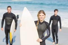 Retrato de los amigos de la persona que practica surf con la tabla hawaiana que se coloca en la playa Imagen de archivo