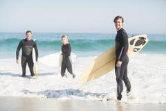 Retrato de los amigos de la persona que practica surf con la tabla hawaiana que se coloca en la playa Imagenes de archivo
