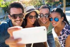 Retrato de los amigos del grupo que toman las fotos con un smartphone Imagen de archivo