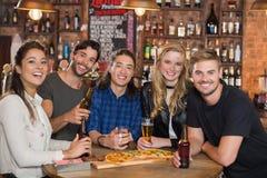 Retrato de los amigos felices que comen pizza con la cerveza Foto de archivo libre de regalías