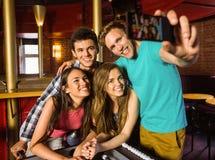 Retrato de los amigos felices que toman una foto con un teléfono Imagen de archivo libre de regalías