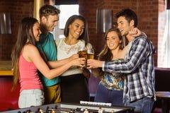 Retrato de los amigos felices que tuestan con la bebida mezclada y la cerveza Imágenes de archivo libres de regalías