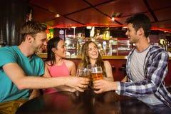 Retrato de los amigos felices que tuestan con la bebida y la cerveza Imagen de archivo libre de regalías