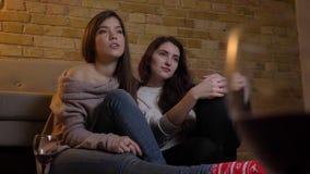 Retrato de los amigos femeninos caucásicos jovenes alegres que ven la TV y que hablan con uno a en fondo casero acogedor almacen de video