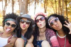 Retrato de los amigos femeninos felices que hacen caras en el sitio para acampar imagenes de archivo