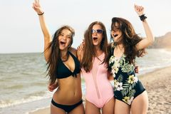 Retrato de los amigos femeninos jovenes que se divierten en la orilla de mar que mira la risa de la cámara El llevar bronceado bo fotografía de archivo libre de regalías