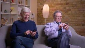 Retrato de los amigos masculinos mayores que se sientan en el silencio cada uno en propio smartphone que está absorbido y ocupado metrajes
