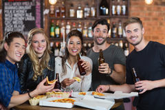 Retrato de los amigos que comen pizza con la cerveza Imagen de archivo libre de regalías