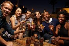 Retrato de los amigos que disfrutan de noche hacia fuera en la barra del tejado Foto de archivo libre de regalías