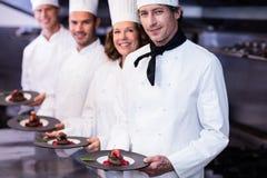 Retrato de los cocineros felices que presentan sus placas de postre Foto de archivo