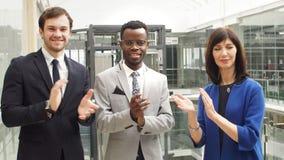 Retrato de los colegas multinacionales del negocio de las manos que aplauden en oficina moderna almacen de video