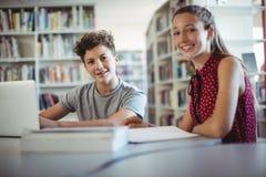Retrato de los compañeros de clase felices que hacen la preparación en biblioteca Imagen de archivo libre de regalías