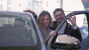 Retrato de los compradores autos sonrientes, pares jovenes gozando del automóvil y mostrando el coche de las llaves en el primer  metrajes