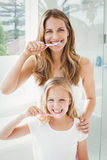 Retrato de los dientes de cepillado sonrientes de la madre y de la hija Imagen de archivo libre de regalías