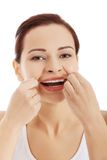 Retrato de los dientes de la limpieza de la mujer con seda dental Fotos de archivo