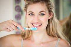 Retrato de los dientes que aplican con brocha sonrientes de la mujer Imagen de archivo