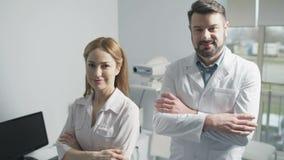 Retrato de los doctores alegres que presentan junto almacen de metraje de vídeo