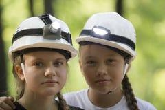 Retrato de los espeleólogos adolescentes lindos de las hermanas en cascos en verano Imágenes de archivo libres de regalías