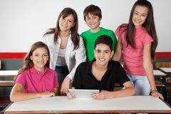 Retrato de los estudiantes adolescentes que usan la tableta en el escritorio Imagenes de archivo