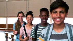 Retrato de los estudiantes felices que se colocan con las carteras en campus almacen de metraje de vídeo