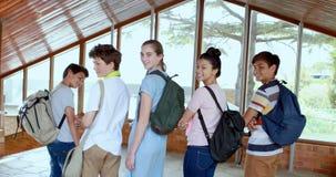 Retrato de los estudiantes felices que se colocan en pasillo metrajes