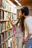 Retrato de los estudiantes que eligen un libro Imagen de archivo libre de regalías