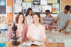 Retrato de los estudiantes que experimentan en el microscopio en laboratorio Fotografía de archivo