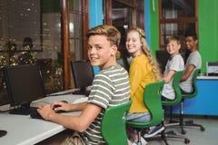 Retrato de los estudiantes sonrientes que estudian en sala de clase del ordenador Foto de archivo