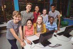 Retrato de los estudiantes sonrientes que estudian en sala de clase del ordenador Imagenes de archivo
