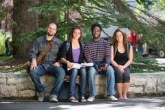 Retrato de los estudiantes universitarios que se sientan en campus Fotos de archivo libres de regalías